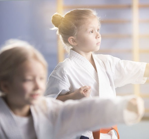 Girl in white kimono practicing karate during extra-curricular class at school